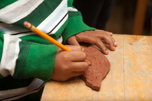 28th Street Elementary School student working on a leaf tile for Juliana Martinez' mural.